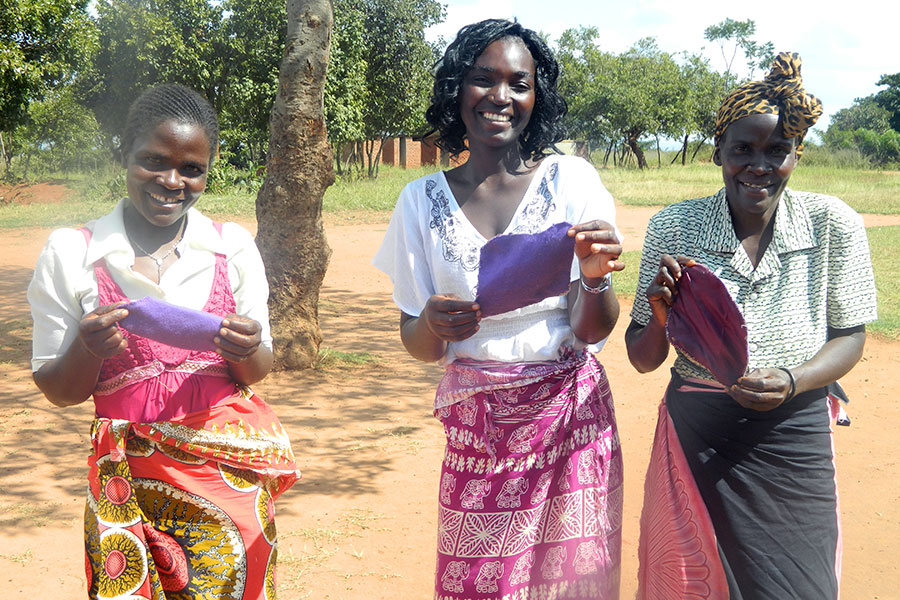 Agness (middle) and mother groups representatives display the pads