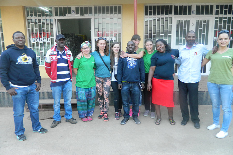 Six of the visitors pose for a photograph with DAPP staff at a DAPP shop in Zomba