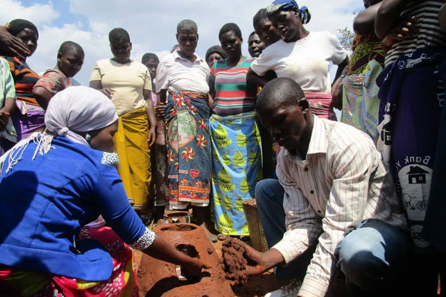 400 Primary Schools Teachers Demonstrate How To Construct Firewood Saving Stoves While Community Members Look On