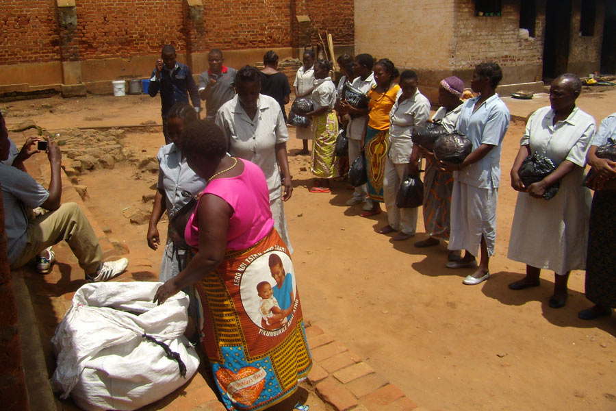 Women Receiving Packs Of Clothes