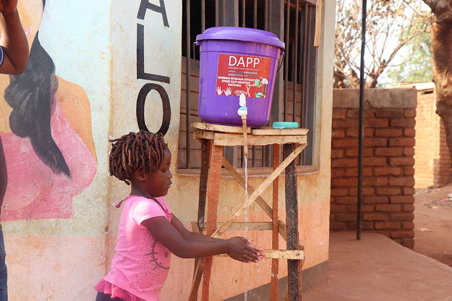 Banda bought a wooden stand for the bucket and ensures that soap is available for washing hands