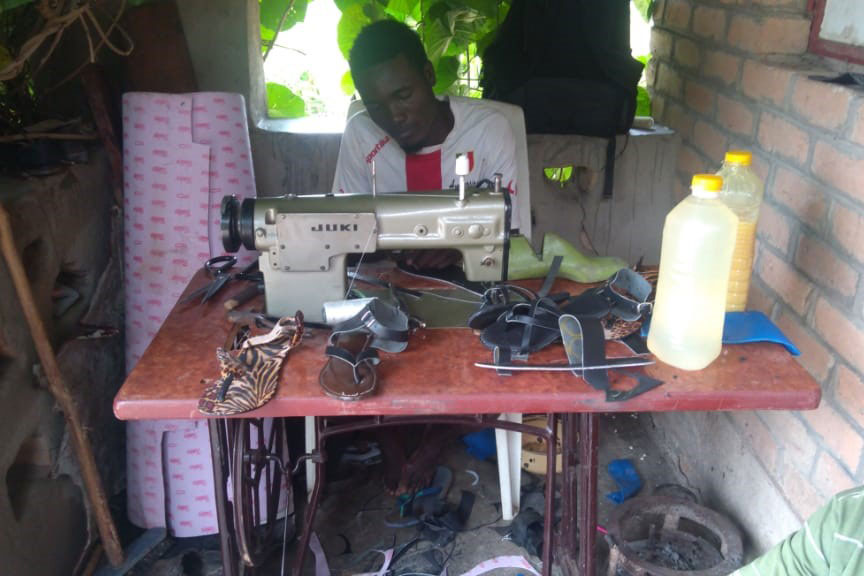 A graduate shoe maker working on his station