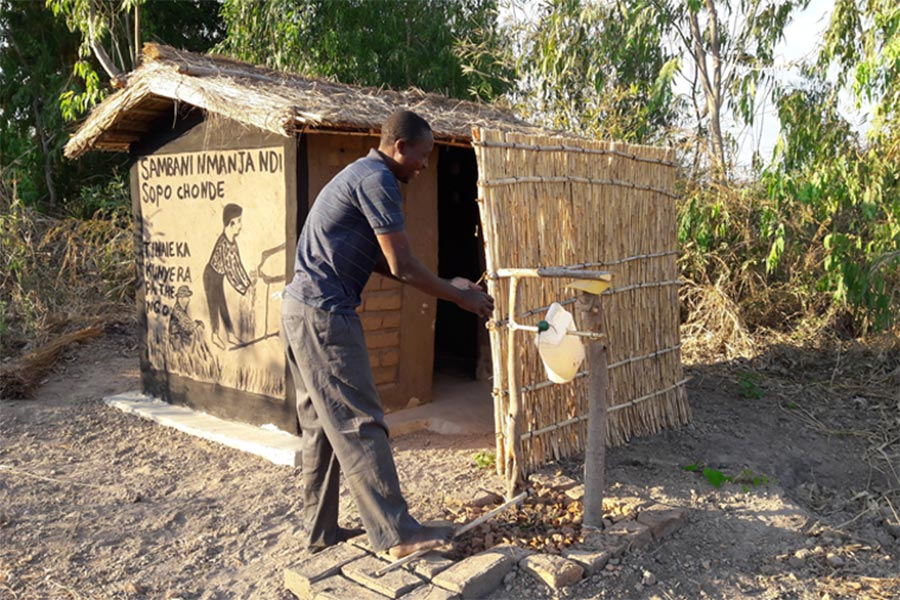Latrines and a hand washing mechanism known as a tippy tap in use