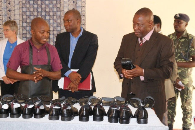 The Minister admiring shoes made by student at Mikolongwe