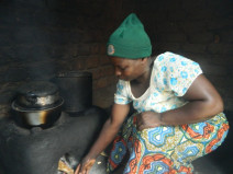 Doreen inserts a piece of firewood into a firewood savingstove in her kitchen